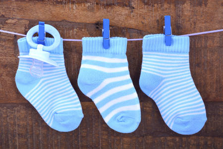 it's: Its a Boy Blue Baby Socks and dummy pacifier hanging from pegs on a line against rustic dark wood background.