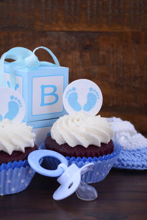 its a boy: Its a Boy blue baby shower cupcake and gift box on vintage dark wood table background. Stock Photo