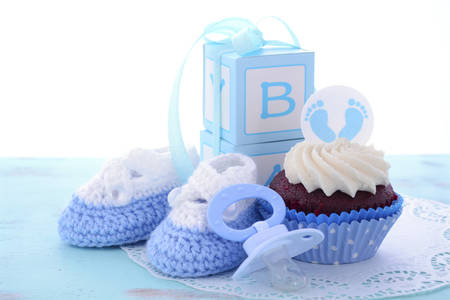 baby shower party: Its a Boy Blue Baby Shower Cupcakes with baby feet toppers and decorations on shabby chic blue wood table.