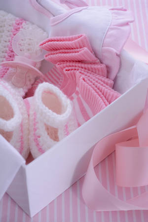 baby shower party: Its a Girl pink theme baby shower gift box with baby clothes, bib, bonnet, booties, pacifier and socks.
