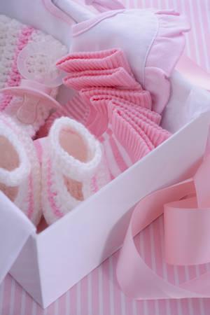 Zijn een meisje roze thema baby shower gift box met babykleren, slab, motorkap, booties, fopspeen en sokken. Stockfoto - 43189725
