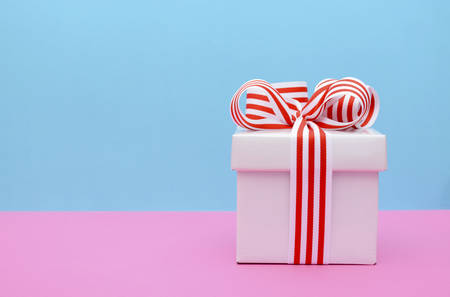 Bright gift box with red and white stripe ribbon on pink and blue background.