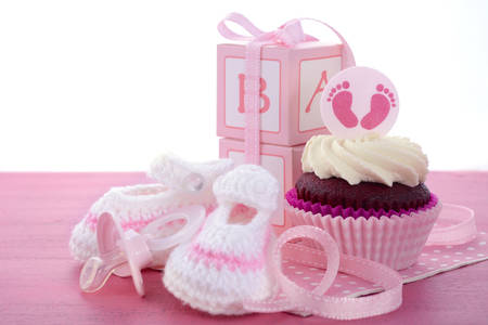 shower: Its a Girl Baby Shower Cupcakes with baby feet toppers and decorations on shabby chic pink wood table. Stock Photo
