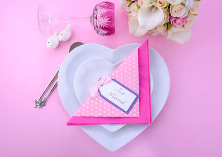 place setting: Modern Wedding Table Place Setting with Heart Shape Plates on Pink Table Background.