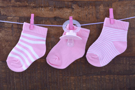 its a girl: Its a Girl Pink Baby Socks and dummy pacifier hanging from pegs on a line against rustic dark wood background.