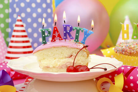 birthday party: Bright colorful Happy Party Table with balloons, streamers, party favor gift bags with slice of cake and lit candles spelling party.