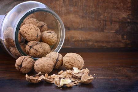 falling out: Fresh walnuts in shells falling out of glass jar on rustic dark wood table background.