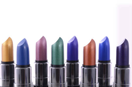 green lipstick: Modern makeup lipstick color range with green, purple, blue, gold, and bronze lipsticks on white background. Stock Photo