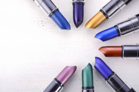 Modern makeup lipstick color range with green, purple, blue, gold, and bronze lipsticks on white wood table background.