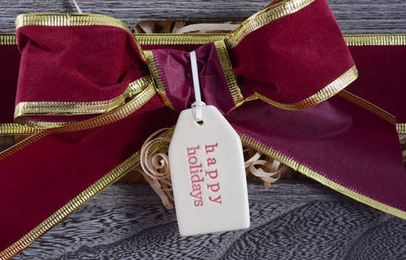hamper: Large Christmas gift hamper with traditional red and green wrapping on red wood table, closeup on Happy Holidays gift tag. Stock Photo
