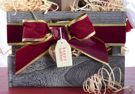 hamper: Large Christmas gift hamper with traditional red and green wrapping on red wood table. Stock Photo