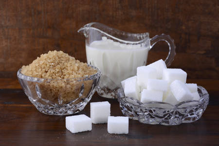 sugar cubes: Cream and sugar in crystal glassware with coffee sugar crystals and sugar cubes on dark vintage wood background.