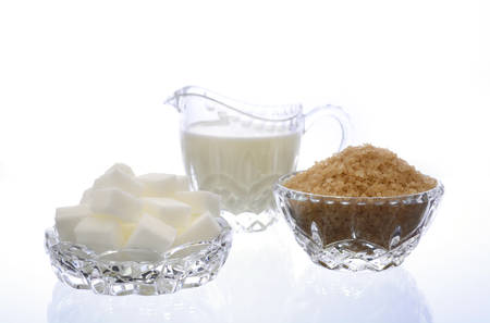 sugar cubes: Cream and sugar in crystal glassware with coffee sugar crystals and sugar cubes on white background.