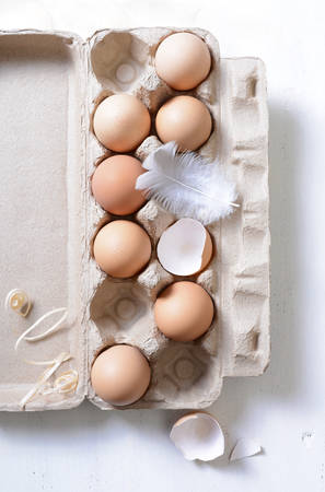 egg carton: Farm fresh eggs in egg carton, with chicken feather and broken shells on white vintage wood table.
