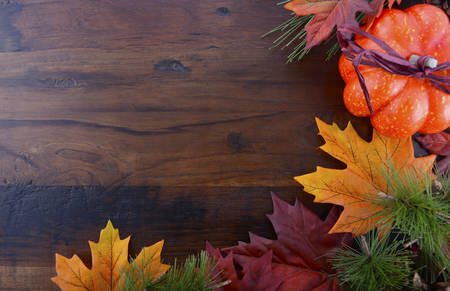 Autumn Fall background for Thanksgiving or Halloween with leaves and decorations on rustic wood table with copy space for your text here. Banque d'images