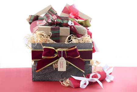 Large Christmas gift hamper with traditional red and green wrapping on red wood table. Stock Photo