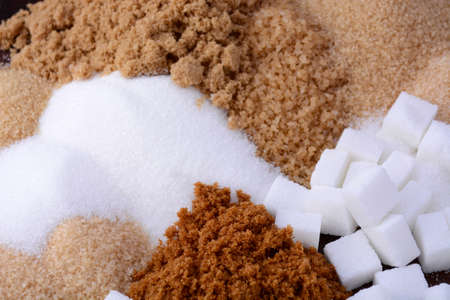 Different types of sugar including white, brown, dark brown, demerara, coffee sugar crystals and sugar cubes.