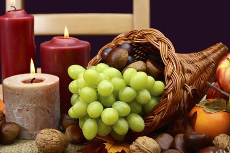 cuerno de la abundancia: Mesa de acción de gracias feliz poniendo en colores rústicos clásicos en la mesa de madera con pieza central cornucopia, velas y frutas.