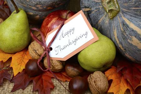 Happy Thanksgiving Pompoen in de rustieke omgeving op jute gedekte tafel met begroeting, close-up.