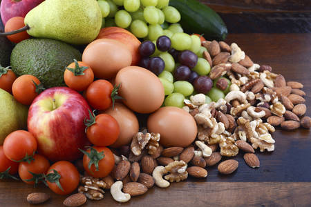 Healthy Diet with fresh fruit, apples, pears, avocados, grapes, eggs, nuts, tomatoes cucumbers on a rustic wood background.
