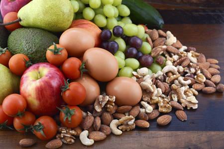 新鮮なフルーツ、リンゴ、梨、アボカド、ブドウ、卵、ナッツ、素朴な木製の背景にトマトきゅうりと健康的な食事。