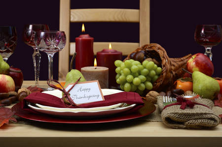 Happy Thanksgiving table setting in classic rustic colors on wood table with cornucopia centerpiece, candles and fruit.