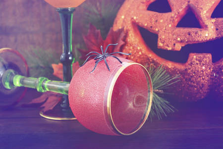 jack o  lantern: Happy Halloween table with Jack O Lantern pumpkin with party wine goblets on rustic dark wood vintage background with added vintage style filters.