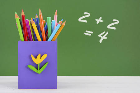 pencil box: Back to school or education concept with colorful purple pencil box against green chalkboard.
