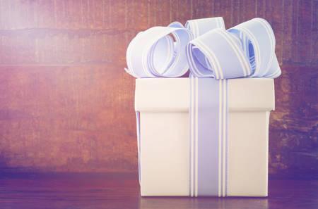 Blauwe en witte gift op donkere houten achtergrond voor mannelijke thema verjaardag of happy Fathers Day aanwezig, met toegevoegde vintage stijl filters en lens flare.