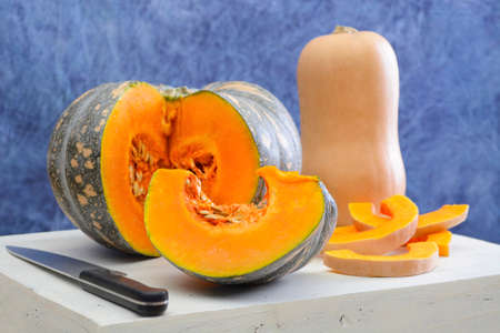 large pumpkin: Food Preparation for Autumn or Thanksgiving meal with cut pumpkin and butternut squash on large white wooden board in blue and white kitchen theme.