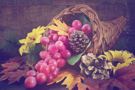 thanksgiving cornucopia: Autumn background with traditional Thanksgiving cornucopia on dark wood table, with added retro vintage style filters. Stock Photo