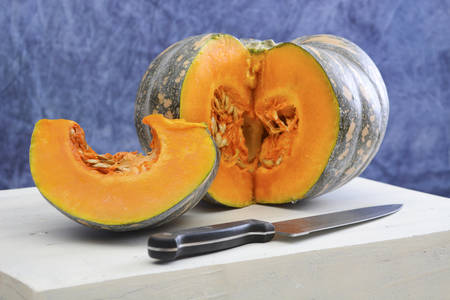 large pumpkin: Food Preparation for Autumn or Thanksgiving meal with cut pumpkin slice on large white wooden board in blue and white kitchen theme. Stock Photo