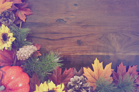 Autumn Fall rustic background on vintage distressed dark wood with autumn leaves and decorations with added retro vintage style filters.