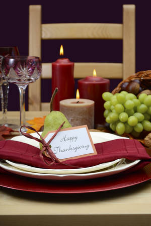 fine cane: Happy Thanksgiving table setting in classic rustic colors on wood table with cornucopia centerpiece, candles and fruit.