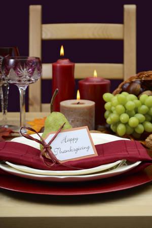 madera rústica: Mesa de acción de gracias feliz poniendo en colores rústicos clásicos en la mesa de madera con pieza central cornucopia, velas y frutas.