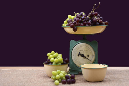kitchen scale: Weighing grapes on vintage scale with old enamel bowls on burlap covered pine table. Stock Photo