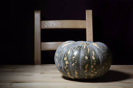 preparations: Solitary pumpkin on rustic pine table with chair for Halloween or Thanksgiving preparations.