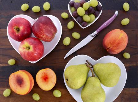 pera: Surtido de frutas, como manzanas, peras, nectarinas y uvas, sobre placas en forma de coraz�n blanco en la mesa de madera r�stica, los gastos generales.