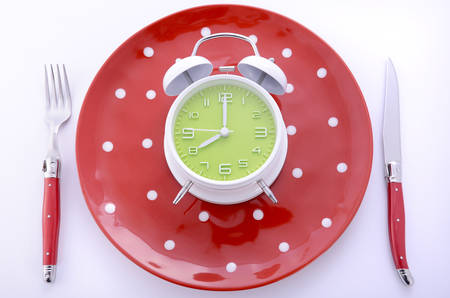 Bright modern table place setting with polka dot plates and cutlery on white background with clock set for eight oclock.
