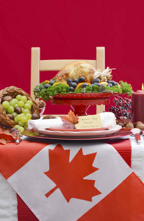 fine cane: Red and white Canadian theme Thanksgiving Table setting with flag and Roast Turkey Chicken on large platter centerpiece . Stock Photo