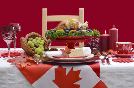 Red and white Canadian theme Thanksgiving Table setting with flag and Roast Turkey Chicken on large platter centerpiece . Stock Photo