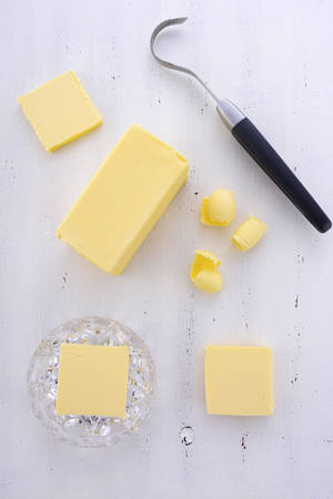 pat: Butter on white wood table with slices, block, crystal butter dish and butter curler utensil.