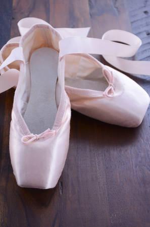 ballet: Pointe zapatos de ballet en el fondo de madera oscura. Foto de archivo