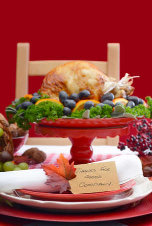 fine cane: Red and white theme Thanksgiving Table setting with Roast Turkey Chicken on large platter centerpiece closeup on Thanks For Good Company place setting, with copy space.