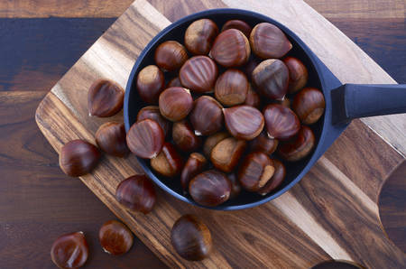 wooden board: Chestnuts in frypan skillet on wooden chopping board against dark wood rustic table. Stock Photo