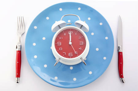 snack time: Bright modern table place setting with blue and red polka dot plates and cutlery on white background with clock set for midnight.