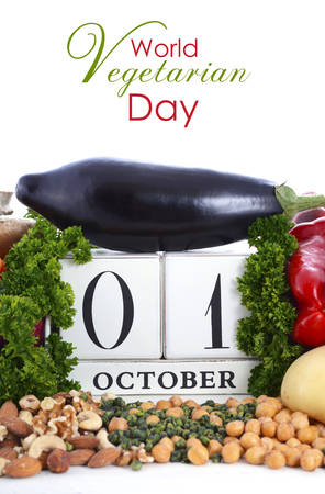 prebiotic: World Vegetarian Day, October 1, vegetables, nuts and legumes surrounding vintage style wood calendar on white background.