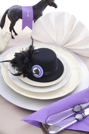 Horse racing Ladies Luncheon fine dining table setting with small black fascinator hat, decorations and champagne.