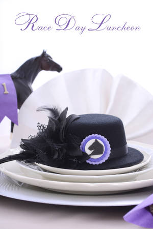 horse race: Horse racing Ladies Luncheon fine dining table setting with small black fascinator hat, decorations and champagne.