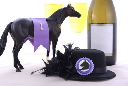 racing: Horse racing Ladies Luncheon fine dining table setting with small black fascinator hat, decorations and champagne.